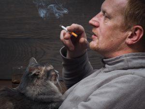 uomo che fuma vicino al gatto