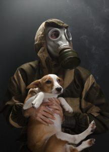 uomo con maschera anti inquinamento e cane in braccio