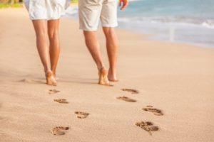 donna e uomo camminano scalzi sulla sabbia