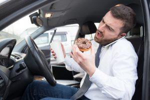 uomo che mangia in macchina mentre parla al telefono