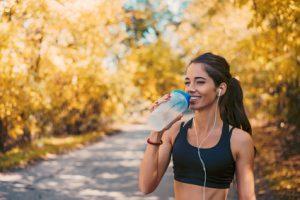 donna che fa attività fisica e beve acqua